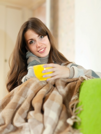 casualy: Girl sitting on sofa in livingroom with cup of tea