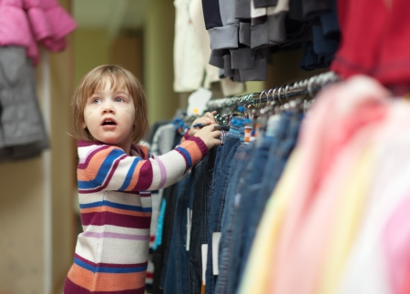 two-year child  chooses jeans at wear shop photo