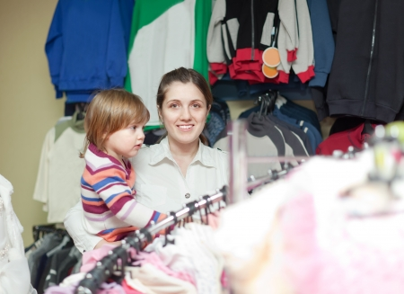 baby girl with cheerful mother chooses wear at clothes store. Focus on woman photo