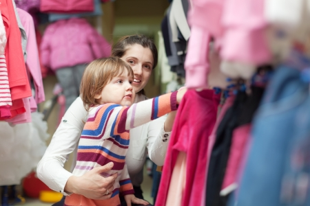 Happy family  chooses wear at fashionable shop. Focus on girl photo