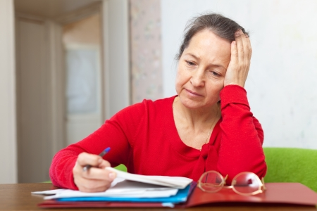 lamentable: Sad mature woman reads documents at home