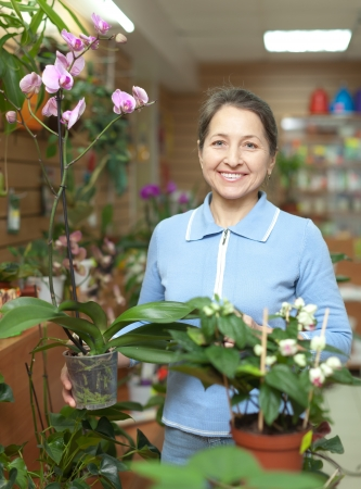 Happy mature woman with  orchid surrounded by different flowers in flower store photo