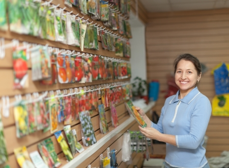 Smiling mature woman chooses the seeds at store photo