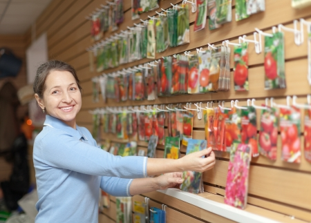 mature woman chooses packed seeds at store   photo