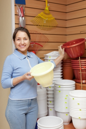 Smiling mature  woman chooses plastic flower pot in the store Stock Photo - 16949237