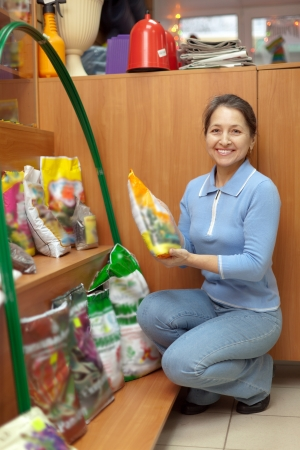 Smiling mature woman chooses fertilizers at garden shop Stock Photo - 16949238