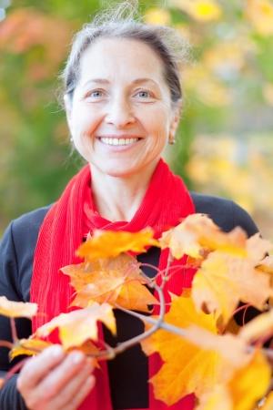 Portrait of happy mature woman  in autumn park Stock Photo - 16949215