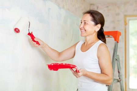 Happy mature woman makes repairs at home Stock Photo - 16949244