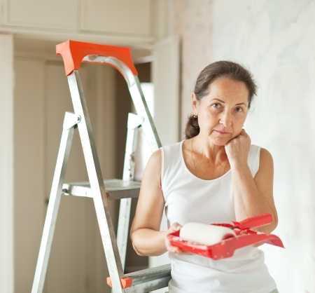 housepainter: weariness mature woman makes repairs at home