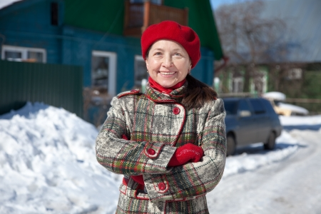 january 1: Happy  mature woman  against her home  in winter