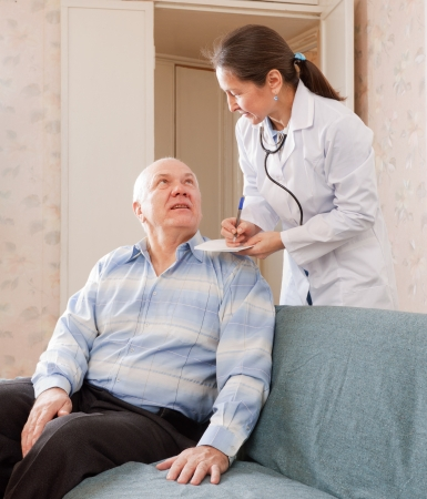 friendly doctor talks with  senior male patient photo