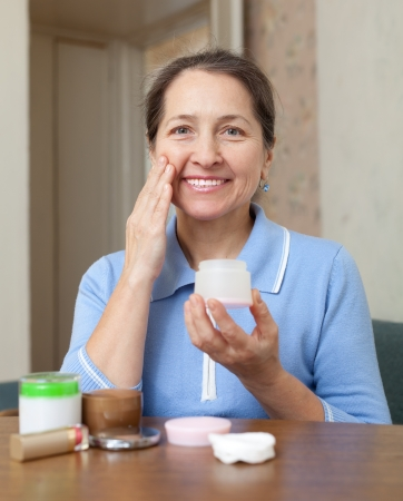 Mature woman puts cream on face at her home Stock Photo - 16964915