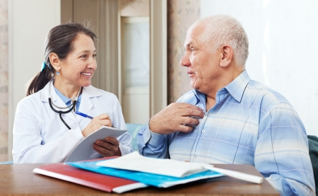 senior man  complaining to friendly doctor about malaise in interior photo