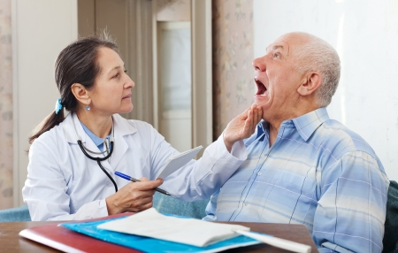 Female mature doctor looks the mouth of senior patient in clinic photo