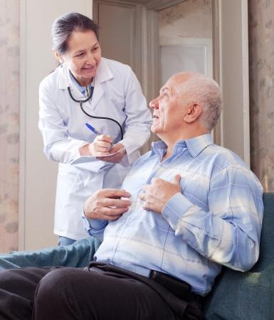 medico con paciente: Hombre mayor que le dice al m�dico maduro los s�ntomas de malestar en el sof�. Foto de archivo