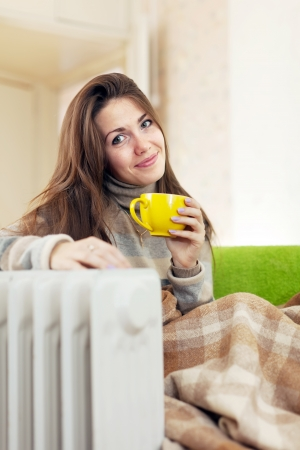 smiling woman  with yellow cup near oil heater Stock Photo - 16973984