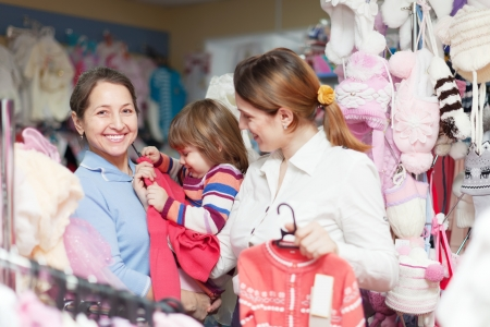 Happy family of three generations chooses wear at childrens clothes shop photo