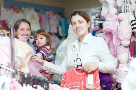 Happy women of three generations chooses wear at clothes store photo