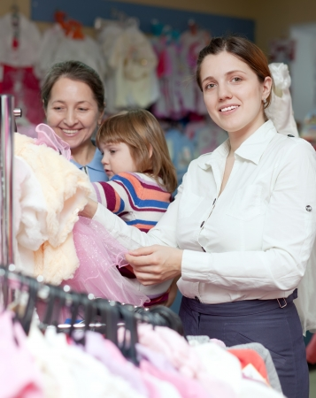 clothing rack: Happy women of three generations  chooses wear at childrens clothes shop. Focus on woman Stock Photo