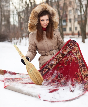 woman cleans red carpet with snow in winter outdoor Stock Photo - 16982507
