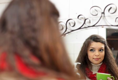 sicken: Colds woman with cup of medicine gargling near mirror  Stock Photo