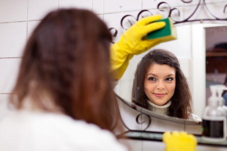 Pretty woman cleans  mirror in bathroom at home photo