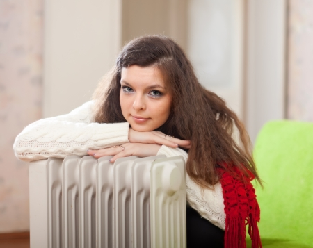 heat register: Portrait of woman  warms near warm heater  in home