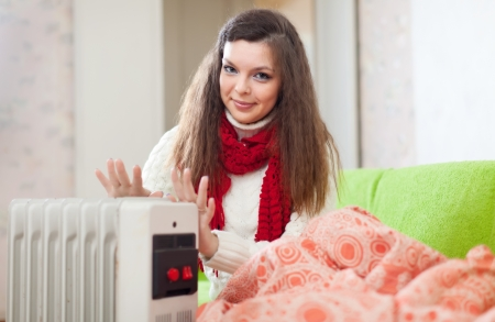 calorifer:  Long-haired woman  near warm radiator  in home Stock Photo