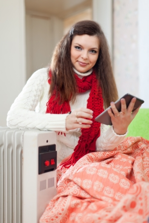 calorifer:  smiling woman  reads eBook near warm radiator  in home