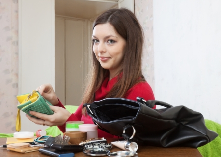 Woman can not finding anything in her handbag at table Stock Photo - 16982372