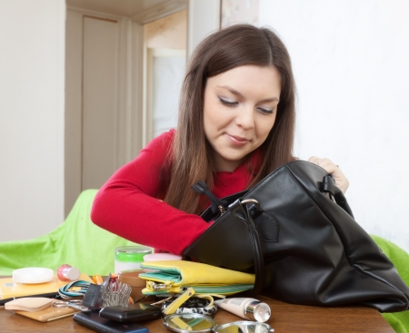 ransack: Pretty girl can not finding anything in her purse at table  Stock Photo