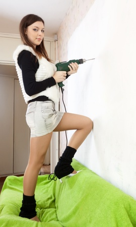 Young woman drill hole in the wall with drill  at home Stock Photo - 16982359