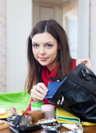 Young woman looking for something in her purse at table Stock Photo - 16982426