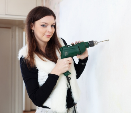 Young woman drill hole in the wall with a drill photo
