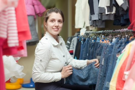 Female buyer chooses jeans at clothing store photo