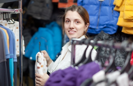 children's wear: Female buyer chooses wear for her little baby at childrens wear store