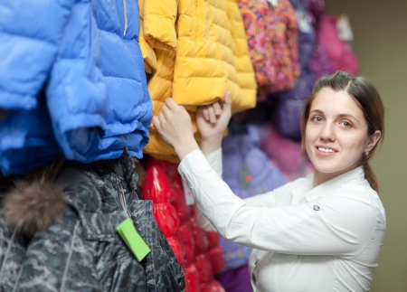 Female buyer chooses the winter jacket in the store photo
