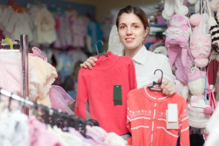 Young woman  chooses children wear at clothing store photo