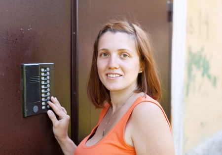 Young woman pushing button of house intercom  outdoor photo