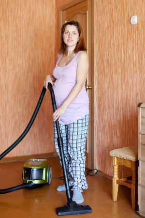 pregnant woman cleans with vacuum cleaner at home Stock Photo - 16994921