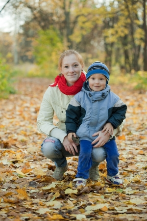 Happy mother with boy in autumn park photo