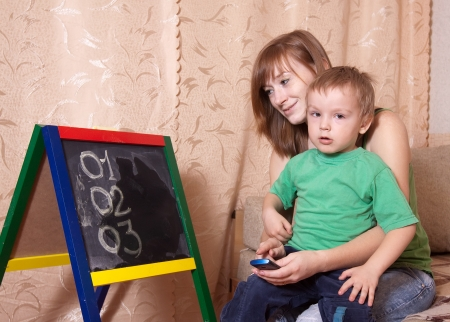 Mother teaches child to emergency phone numbers Stock Photo