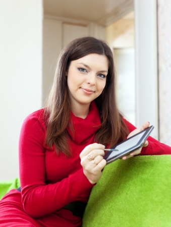 Smiling woman with tablet computer or electronic book on sofa at home photo
