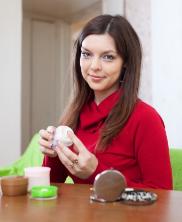 Pretty young woman uses cosmetic cream in home Stock Photo - 17031487