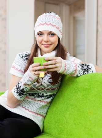 casualy: Pretty woman in hat warms with cup of tea at house in winter