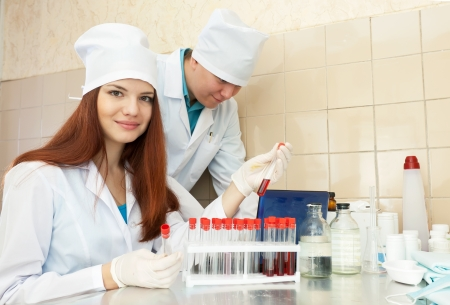 Male doctor supervises the young nurse in medical lab photo