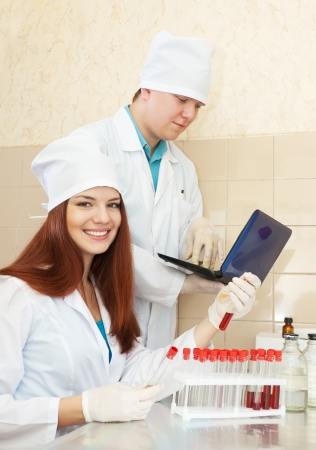 Positive nurse and male doctor works with test tubes in clinic lab  Stock Photo - 17051884
