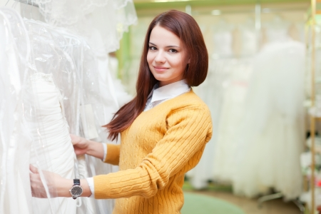 woman chooses white dress at shop of wedding fashion photo