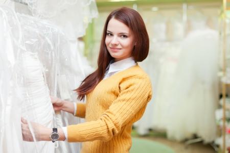 bridal salon: woman chooses white dress at shop of wedding fashion