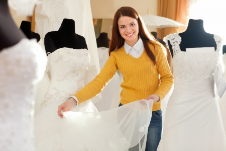 Young woman chooses wedding gown at bridal boutique photo